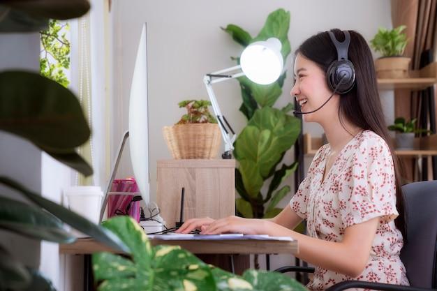 Azjatycka kobieta rozmawia z innymi członkami spotkania przez komputer stacjonarny i konferencję vidio. ten obraz można wykorzystać do pracy z domu, covid19, biura domowego i koncepcji firmy