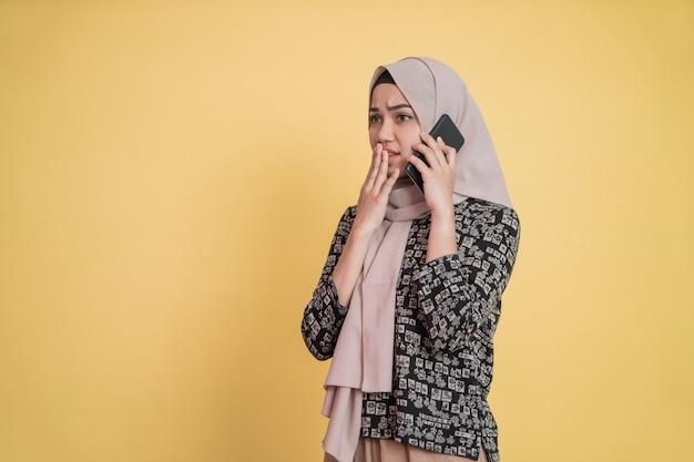 Azjatycka kobieta rozmawiająca przez telefon za pomocą telefonu komórkowego ze zmartwionym wyrazem twarzy