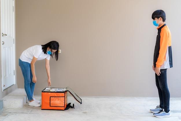 Azjatycka kobieta rozpakowuje i odbiera dostarczoną torbę z jedzeniem z pudełka i dla bezkontaktowego lub bezkontaktowego jeźdźca z rowerem przed domem w celu zachowania dystansu społecznego dla ryzyka infekcji.
