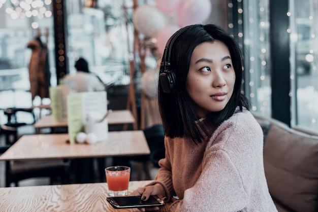 Azjatycka kobieta sama w mieście siedzi w kawiarni i słucha muzyki. ciesz się muzyką w miejscu publicznym