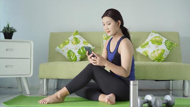 Azjatycka kobieta siedząca zrelaksowana grająca na telefonie po zakończeniu jogi w domu