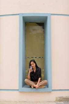 Azjatycka kobieta siedzi i relaksuje się podczas korzystania z telefonu komórkowego w mieście