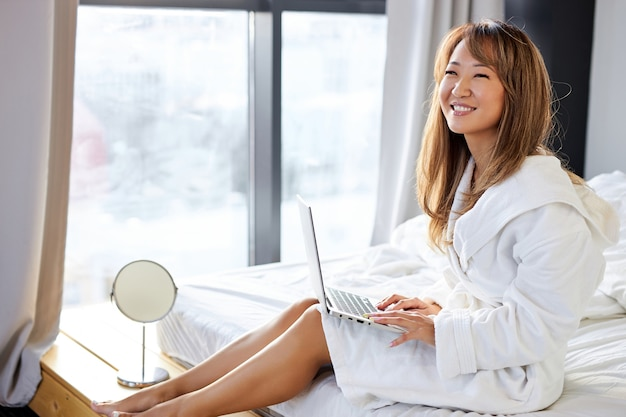 Azjatycka kobieta siedzi na szerokim białym łóżku za pomocą nowoczesnego laptopa, rozmawiając z kimś online