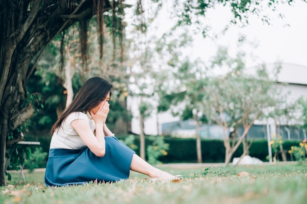 Azjatycka kobieta siedzi samotnie i deprymuje, portret zmęczona młoda kobieta. depresja