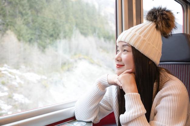 Azjatycka kobieta siedzi w pociągu i patrzeje przez okno