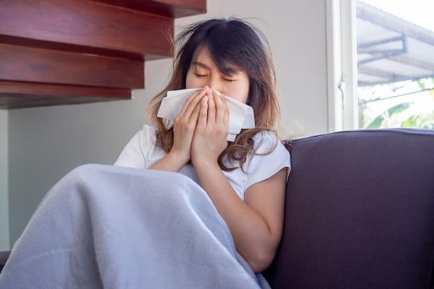 Azjatycka kobieta siedziała chora na kanapie w domu, mając gorączkę, kaszel, kichanie i zatkany nos. zakrywając nos kawałkiem papieru.