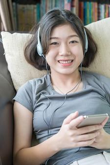 Azjatycka kobieta słucha muzykę z telefonu komórkowego