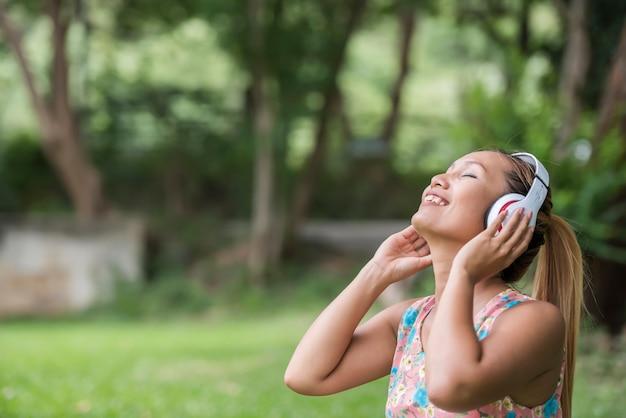 Azjatycka kobieta słucha ulubioną muzykę na hełmofonach. szczęśliwy czas i relaks.