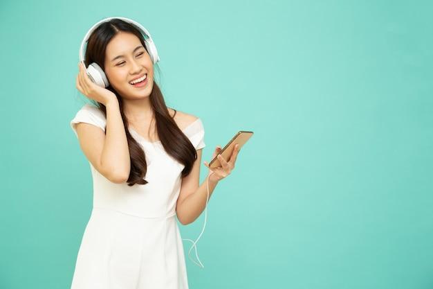 Azjatycka kobieta słuchająca muzyki przez słuchawki na telefonie komórkowym na zielonym tle