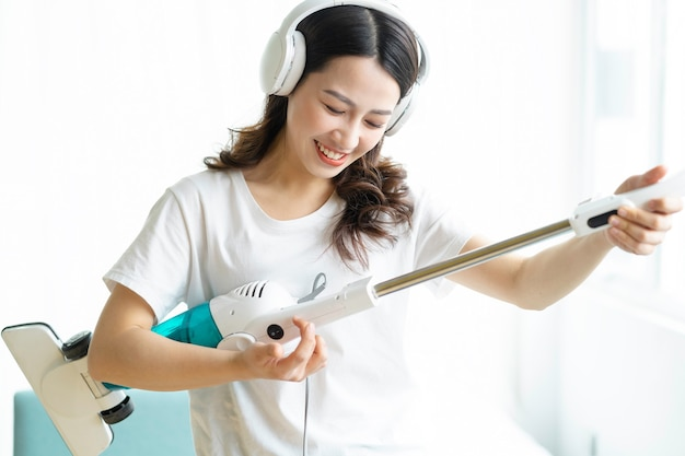 Azjatycka kobieta, słuchanie muzyki i taniec z odkurzaczem