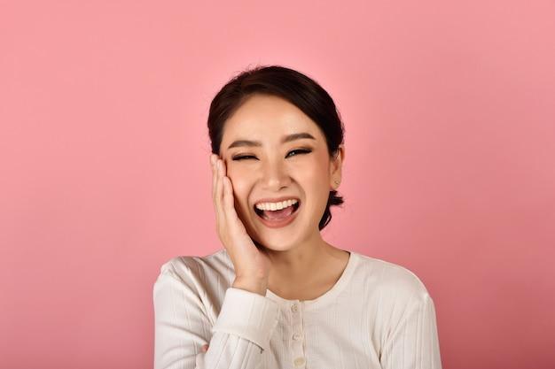 Azjatycka kobieta śmia się i cieszy się na menchii ścianie