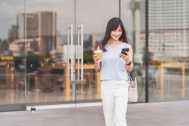 Azjatycka kobieta spacerująca po mieście, korzystająca z telefonu komórkowego i trzymająca papierowy kubek z kawą