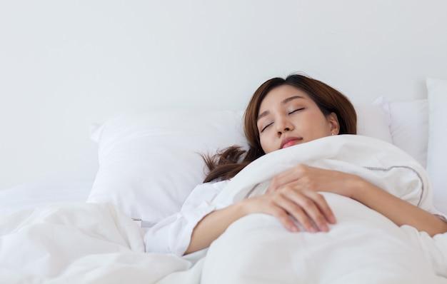 Azjatycka kobieta śpi w białym łóżku na wakacjach w domu.