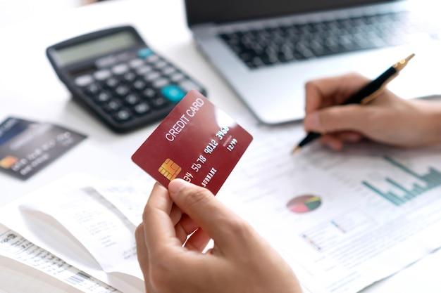 Azjatycka kobieta sprawdza rachunki, saldo konta bankowego i oblicza wydatki karty kredytowej. wydatki rodzinne, koncepcja biznesu i finansów