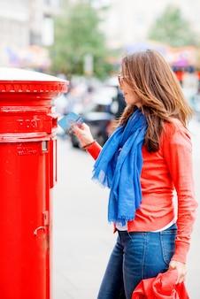 Azjatycka kobieta stawia kartę czerwony postbox i chodzi wokoło angielskiego miasta