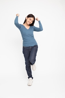 Azjatycka kobieta stoi i ręce w górę uniesione ramiona ze szczęścia na białym tle