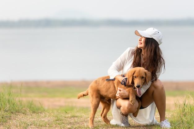 Azjatycka kobieta styl życia bawi się z psem przyjaźnią golden retrievera tak szczęśliwa i relaksująca na świeżym powietrzu w letnim parku łąkowym.