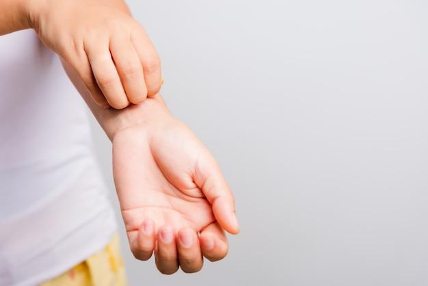 Azjatycka kobieta swędzi jej używać swędzącego ręka swędzenie