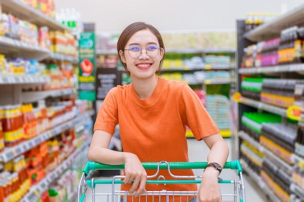 Azjatycka kobieta szczęśliwa zakupy w centrum handlowym obsługuje wózek na zakupy z półką w supermarkecie