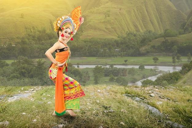 Azjatycka kobieta tańczy balijski tradycyjny taniec (taniec kembang girang) na polu