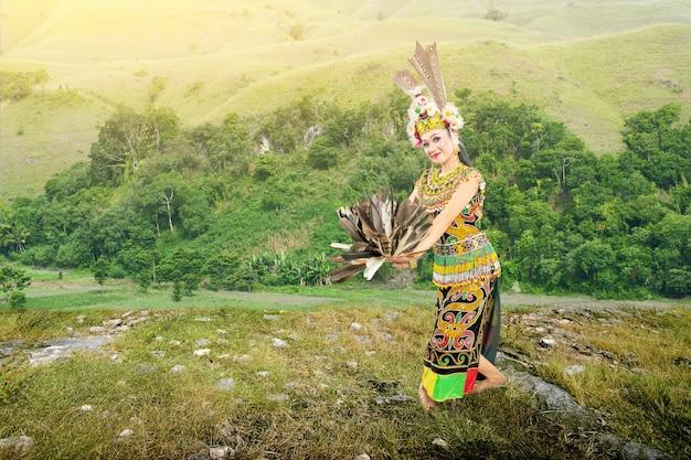 Azjatycka kobieta tańczy tradycyjny taniec wschodniego kalimantanu (taniec giring-giring) na polu