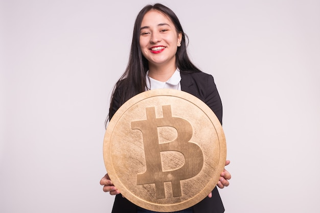 Azjatycka kobieta trzyma duże bitcoiny na białej ścianie. koncepcja inwestycji kryptowalutowych.