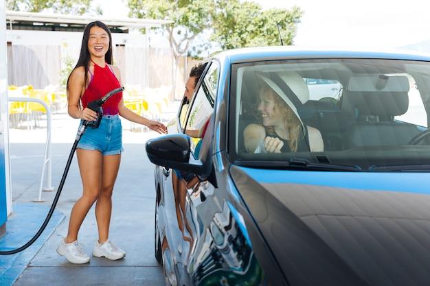 Azjatycka kobieta trzyma dyszę gazową i otwiera zbiornika podczas gdy przyjaciele siedzi w samochodzie