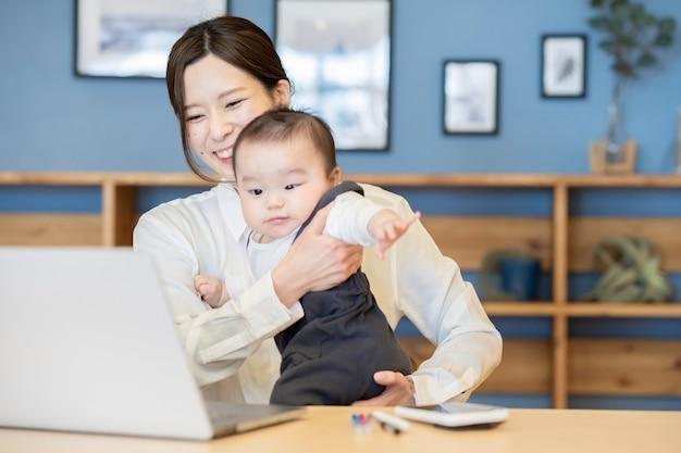 Azjatycka kobieta trzyma dziecko i obsługi laptopa w pomieszczeniu