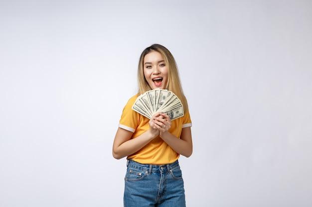 Azjatycka kobieta trzyma gotówkowe notatki odizolowywać w białym tle