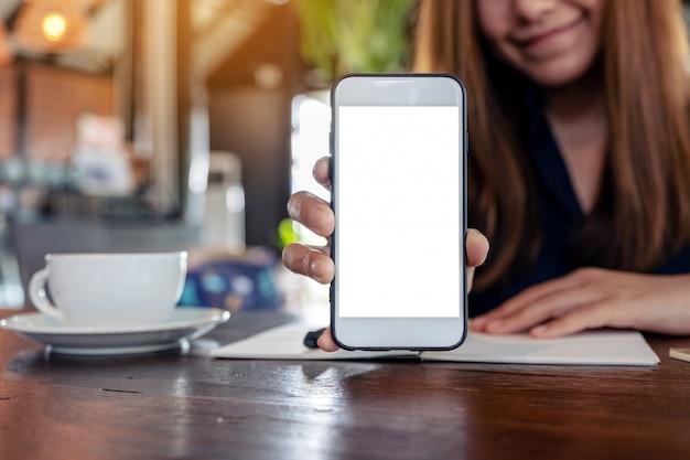 Azjatycka kobieta trzyma i pokazuje biały telefon komórkowy z pustym ekranem pulpitu z filiżankami do kawy i notatnikami na vintage drewnianym stole w kawiarni