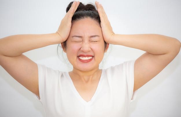 Azjatycka kobieta trzyma jej ręki głowa w bólu i ma problemy zdrowotne na bielu
