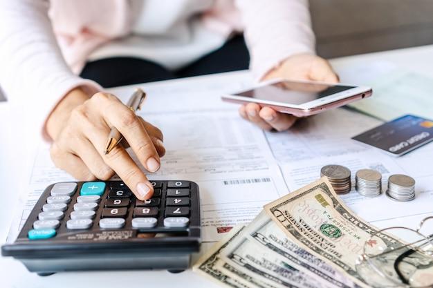Azjatycka kobieta trzyma mądrze telefon podczas gdy używać kalkulatora na biurku