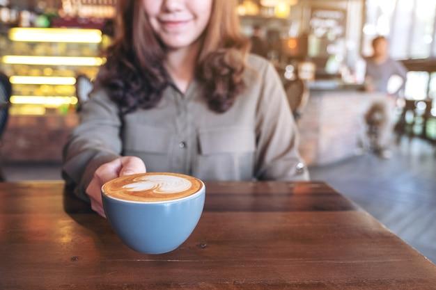 Azjatycka kobieta trzyma niebieską filiżankę gorącej kawy latte ze sztuką latte na drewnianym stole w kawiarni