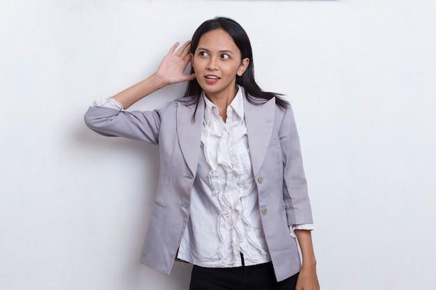 Azjatycka kobieta trzyma rękę przy uchu i słucha