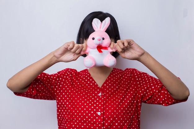Azjatycka kobieta trzyma różową lalkę króliczka w koncepcji miłości i walentynek