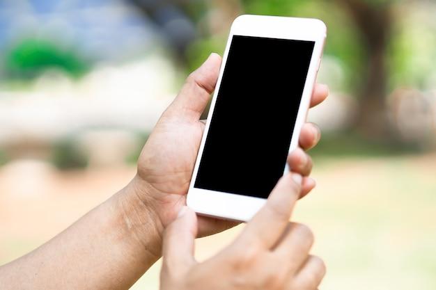 Azjatycka kobieta trzyma telefon komórkowy do komunikacji w biznesie.