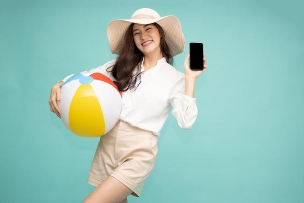 Azjatycka kobieta trzyma telefon komórkowy i piłkę plażową na białym tle na zielonym tle