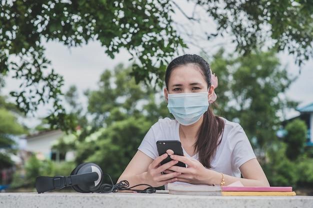 Azjatycka kobieta trzyma telefon z maską na twarzy