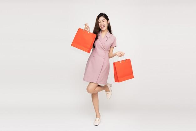 Azjatycka kobieta trzyma torby na zakupy w całym ciele.