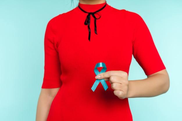 Azjatycka kobieta trzyma w ręku niebieską wstążkę. symbol problem wykorzystywania dzieci i raka prostaty