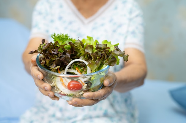 Azjatycka kobieta trzyma warzywo.