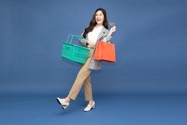 Azjatycka kobieta trzymająca torby na zakupy, kosz i kartę kredytową na białym tle na niebieskim tle