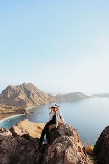 Azjatycka kobieta turystka w okularach przeciwsłonecznych i letnim kapeluszu siedząca na szczycie wzgórza na wyspie padar