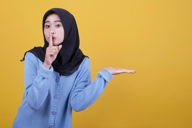 Azjatycka kobieta ubrana w hidżab przestaje mówić gestem i coś pokazuje