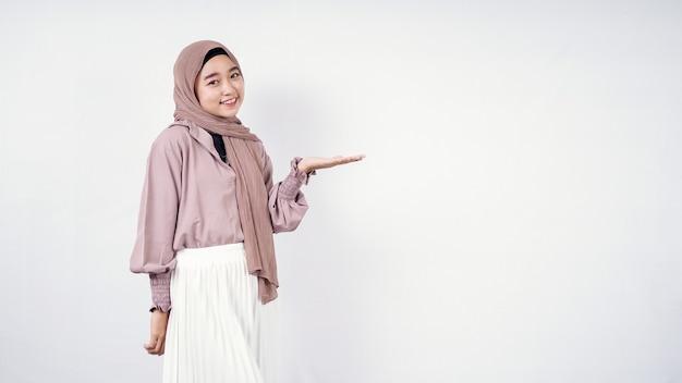 Azjatycka kobieta ubrana w hidżab, wskazując pustą przestrzeń obok na białym tle