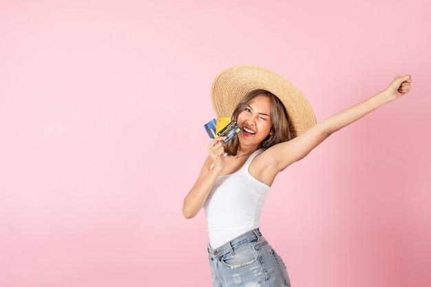 Azjatycka kobieta ubrana w letnią sukienkę, trzymająca kartę kredytową i podnosząca rękę