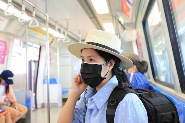 Azjatycka kobieta ubrana w maskę węglową do ochrony smogu lub pm 2.5 i wirusów w pociągu metra