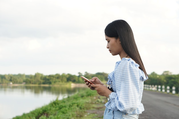 Azjatycka kobieta ubrana w niebieską sukienkę używa tła natury telefonu komórkowego