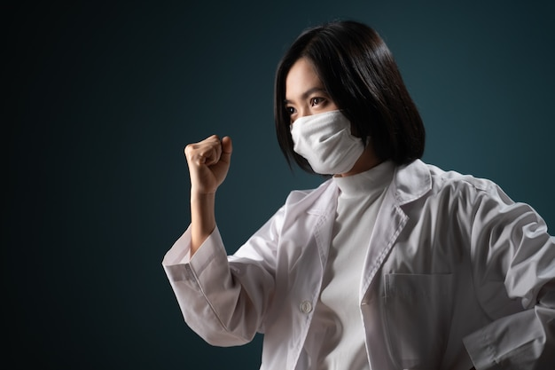 Azjatycka kobieta ubrana w ochronną maskę na twarz i mundur medyczny wykonuje zwycięski gest na niebiesko