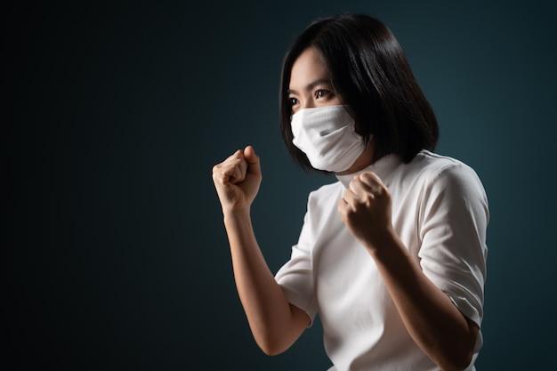 Azjatycka kobieta ubrana w ochronną maskę na twarz sprawia, że zwycięski gest jest odizolowany na niebiesko
